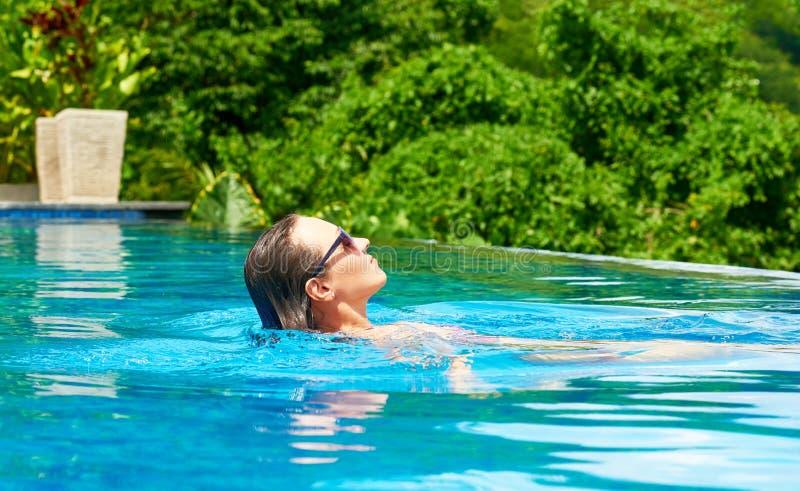 Attraktiv kvinna med baddräktsimning på en pöl för blått vatten royaltyfri foto