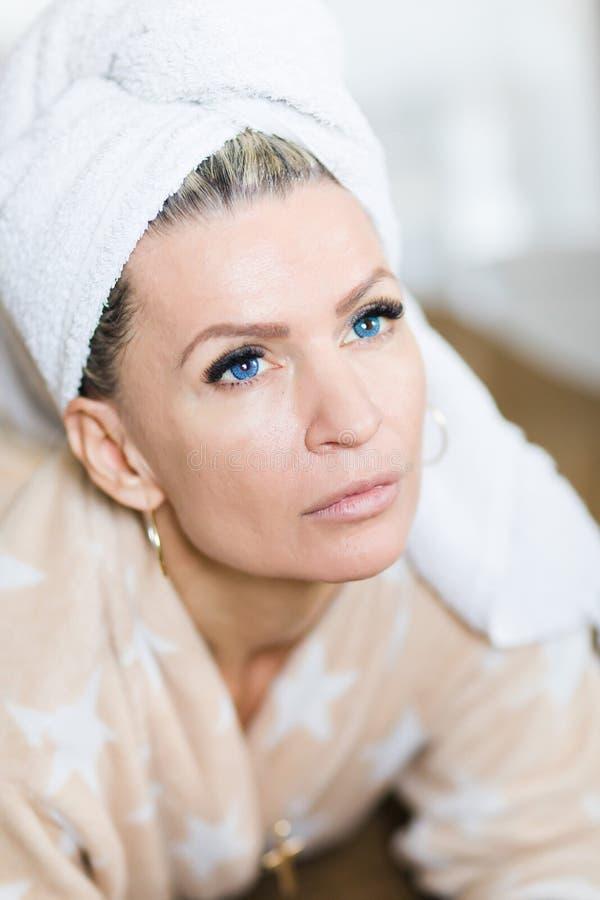 Attraktiv kvinna med blåa ögon med handduken på huvudet efter relaxat royaltyfri bild