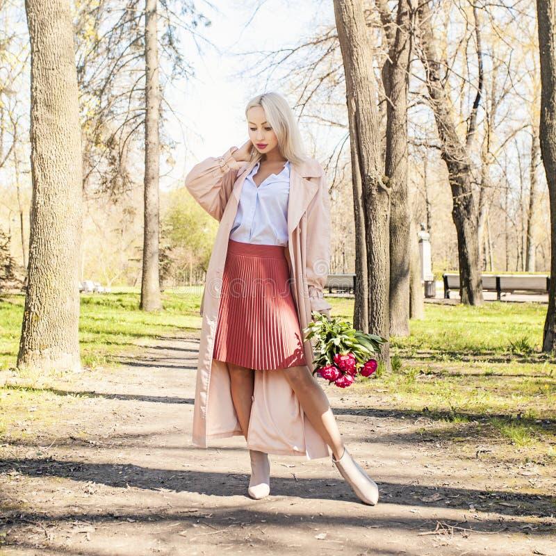 Attraktiv kvinna med blommor utomhus arkivfoto