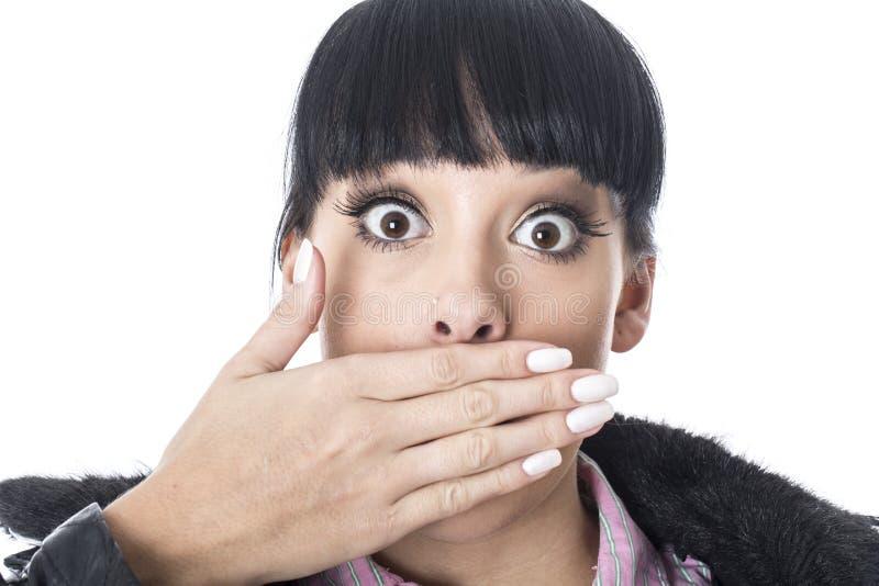 Attraktiv kvinna med chockat uttryck med ögon vitt och handen över mun arkivfoton