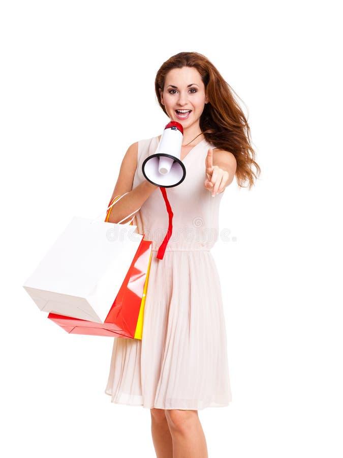 Attraktiv kvinna med den shoppingpåsar och megafonen fotografering för bildbyråer