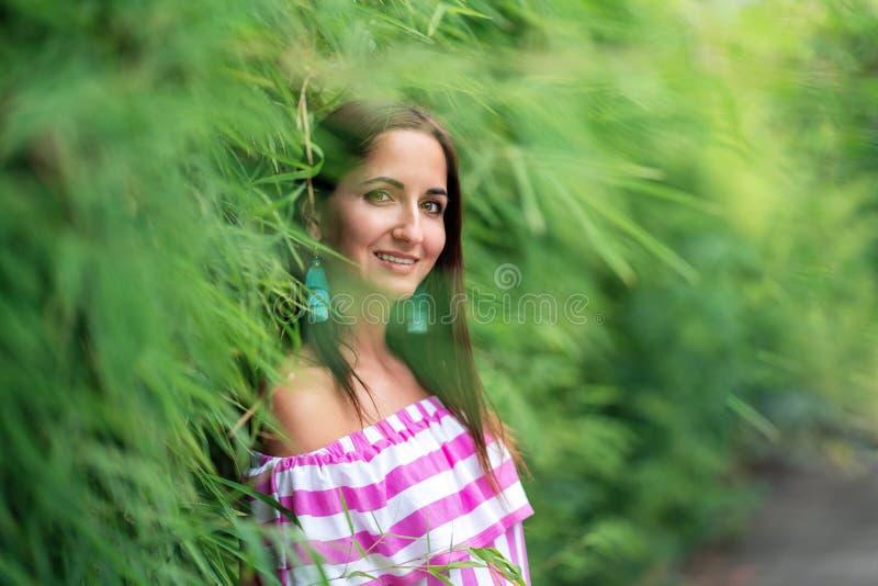 Attraktiv kvinna med ett leende som står nära en grön häck av gräs royaltyfria bilder