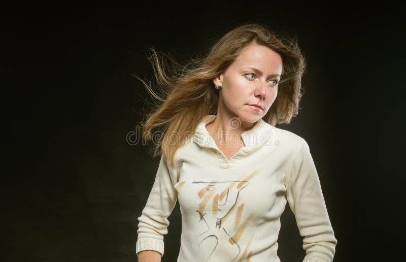 Attraktiv kvinna med hår som fladdrar i vinden på svart bakgrund Lugna och jämn till humöret flicka i beigea omslagsblickar arkivfoto