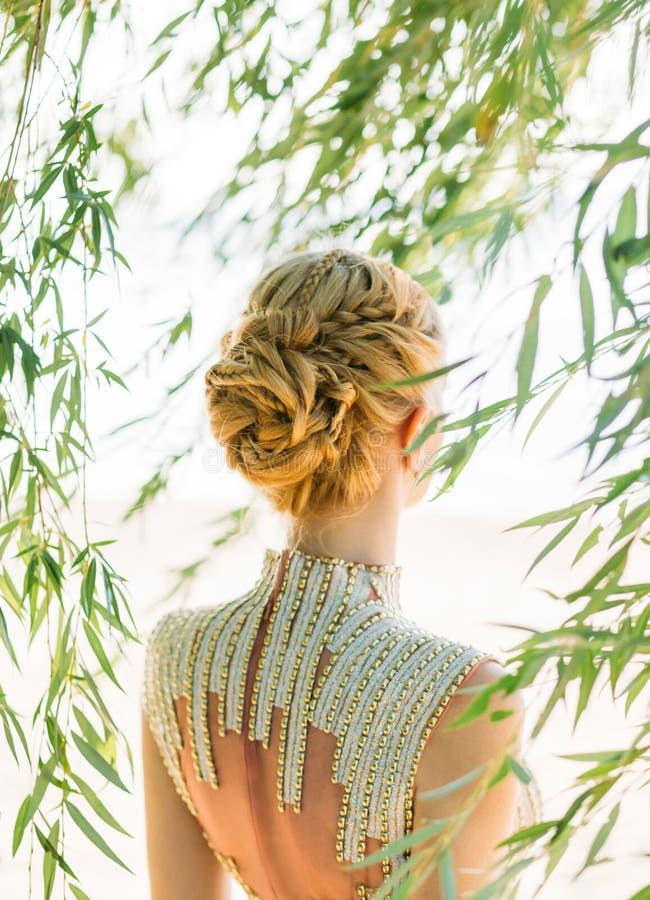 Attraktiv kvinna med rakt blont blont hår som flätas i en mjuk frisyr av flätade trådar för en prinsessa eller en älva som är pro royaltyfria foton