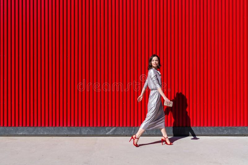 Attraktiv kvinna mot en röd vägg utomhus royaltyfria bilder