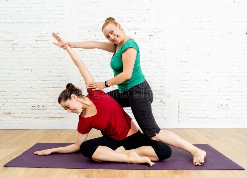 Attraktiv kvinna och yogalagledare som hjälper hennes praktiserande yogaövning i sunt livsstilbegrepp royaltyfri bild
