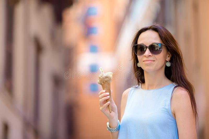 Attraktiv kvinna på gatan som har roligt och äter glass Y fotografering för bildbyråer
