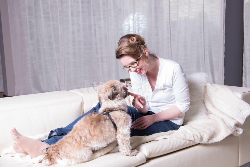 Attraktiv kvinna på soffan med hennes hund royaltyfri fotografi