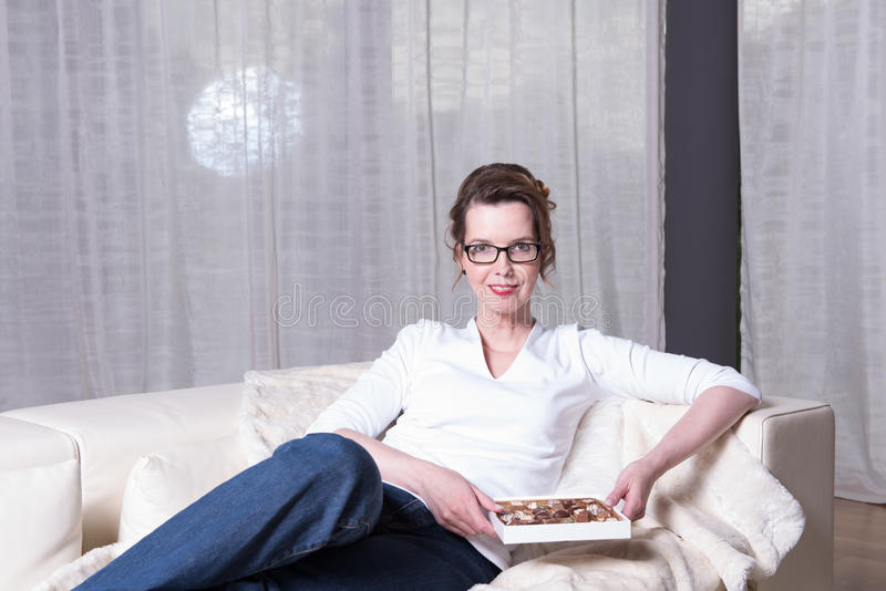 Attraktiv kvinna på soffan som äter choklad fotografering för bildbyråer