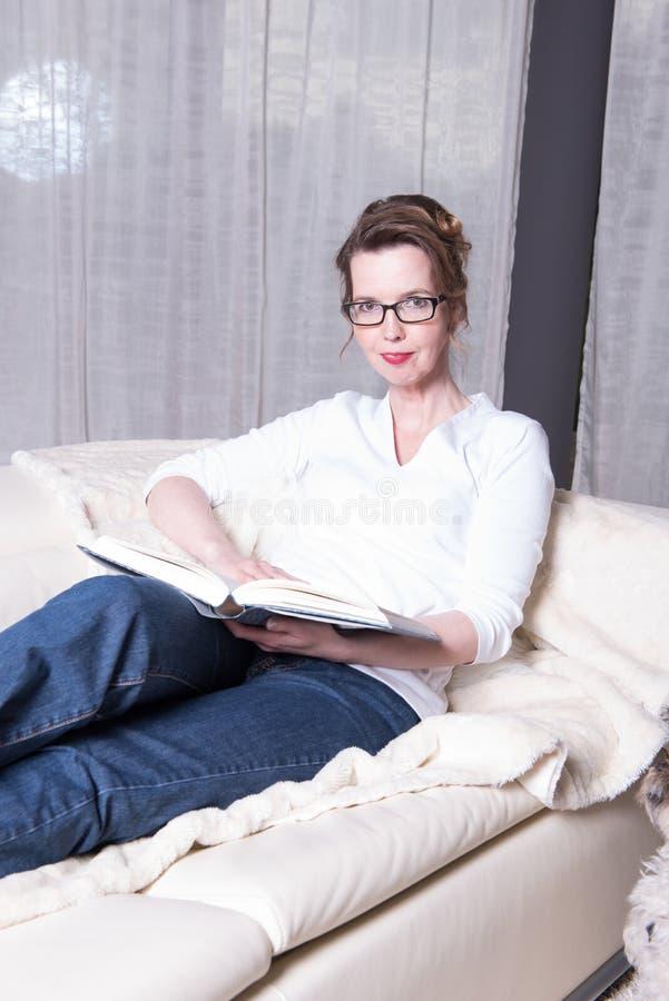 Attraktiv kvinna på soffan som läser en bok arkivfoton