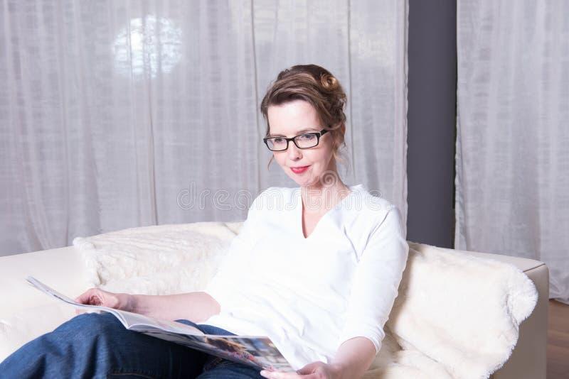 Attraktiv kvinna på soffan som läser en tidskrift arkivbild