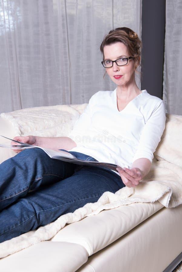 Attraktiv kvinna på soffan som läser en tidskrift arkivbilder