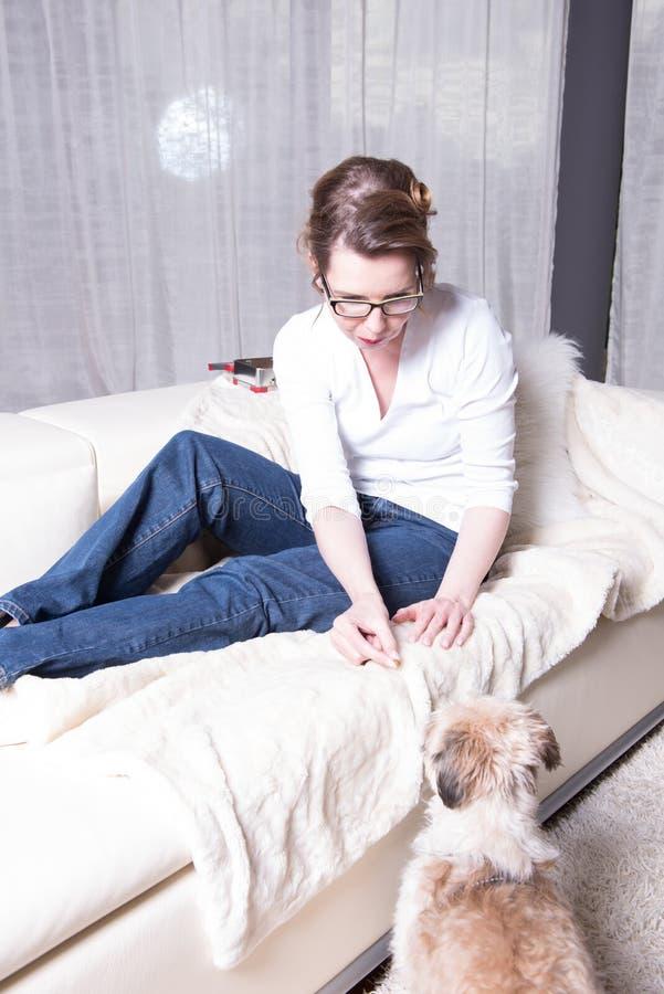 Attraktiv kvinna på soffan som matar hennes hund arkivfoto