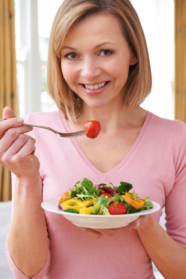 Attraktiv kvinna som äter sund sallad royaltyfria foton