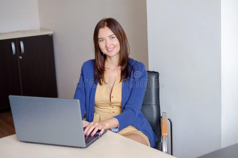 Attraktiv kvinna som arbetar på bärbara datorn i start-up kontor arkivfoton