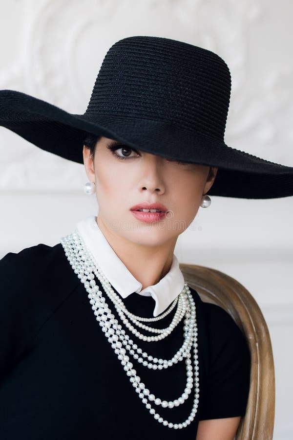 Attraktiv kvinna som bär den svarta klänningen, hatten och pärlor som sitter på stol arkivbilder