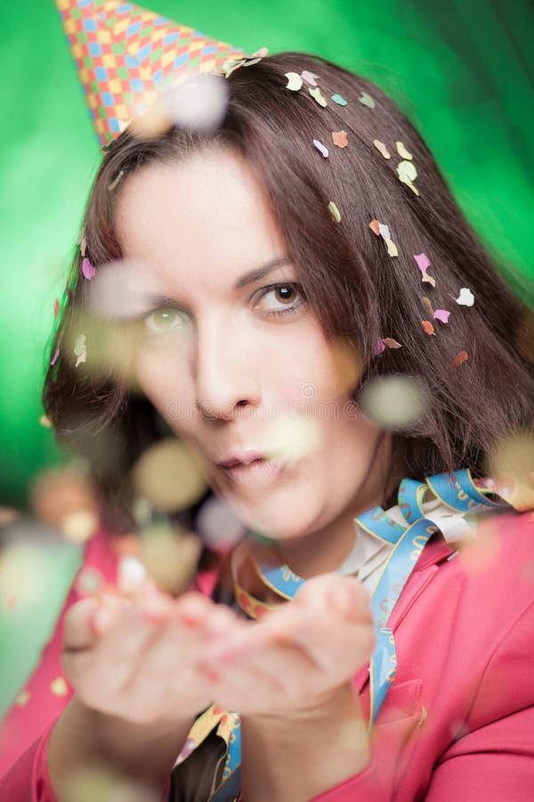 Attraktiv kvinna som blåser konfettier och att fira royaltyfri foto