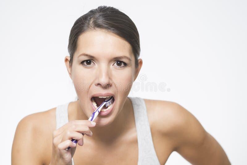 Attraktiv kvinna som borstar hennes tänder royaltyfri fotografi