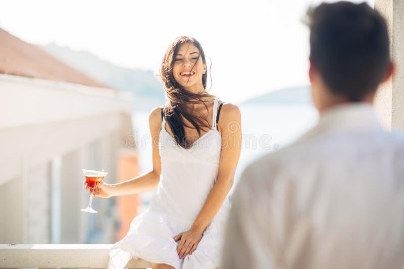 Attraktiv kvinna som dricker coctailen och tycker om hennes sommarsemester Dricka den uppfriskande drinken och le till en man royaltyfria foton