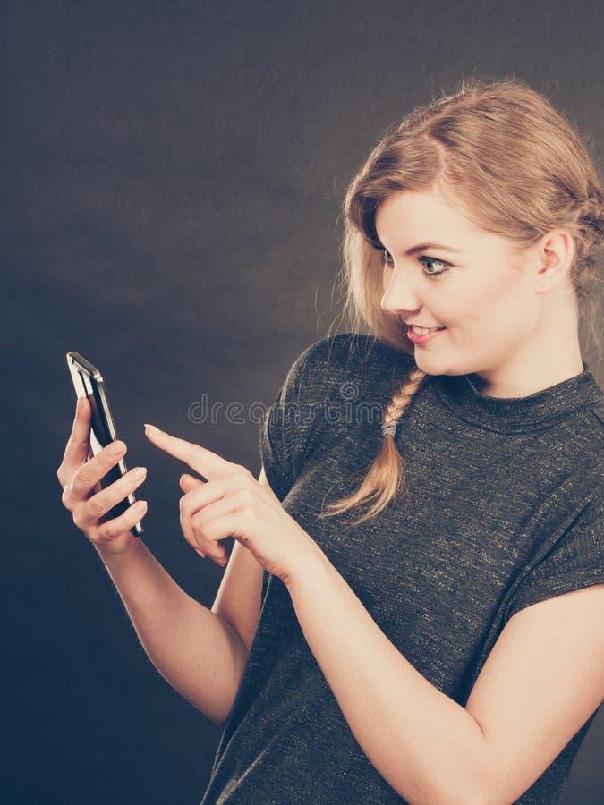 Attraktiv kvinna som flörtar att smsa på mobiltelefonen arkivfoton