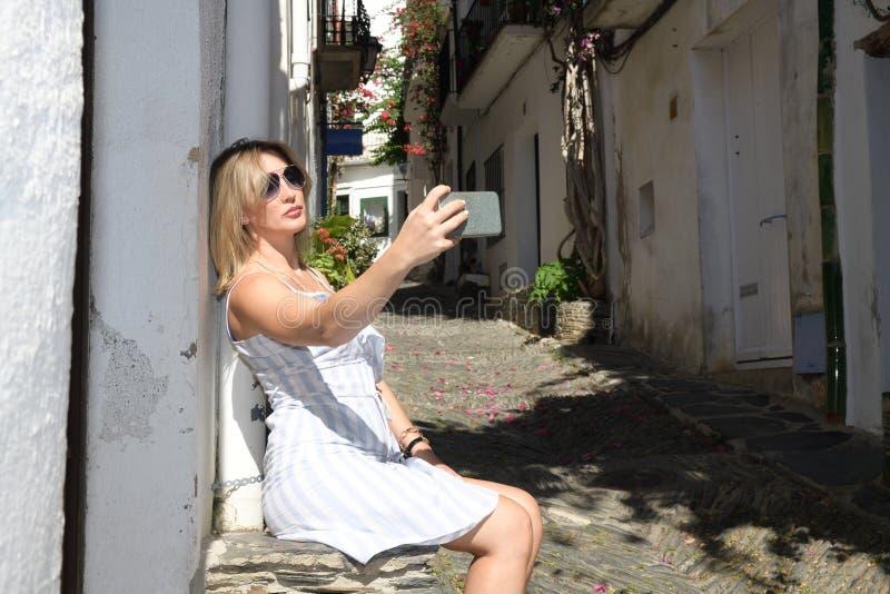 Attraktiv kvinna som gör en selfie i gatan av en forntida medelhavs- by arkivfoton
