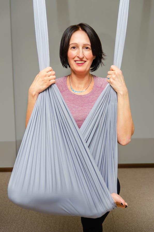 Attraktiv kvinna som gör flugayoga i en hängmatta i studion royaltyfri foto