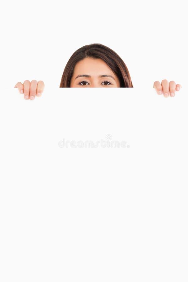 Attraktiv kvinna som hidding bak ett bräde arkivbild