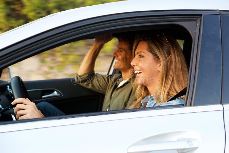 Attraktiv kvinna som kör bilen med pojkvännen bredvid henne royaltyfri fotografi