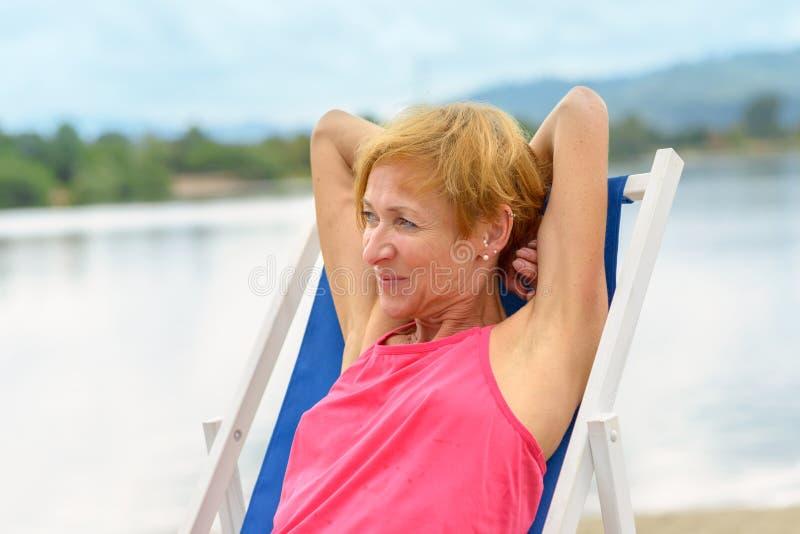 Attraktiv kvinna som kopplar av förbise en sjö royaltyfri bild