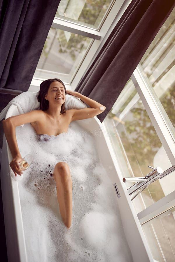 Attraktiv kvinna som kopplar av i bad med bästa sikt för skum- och drinkchampagne arkivbilder