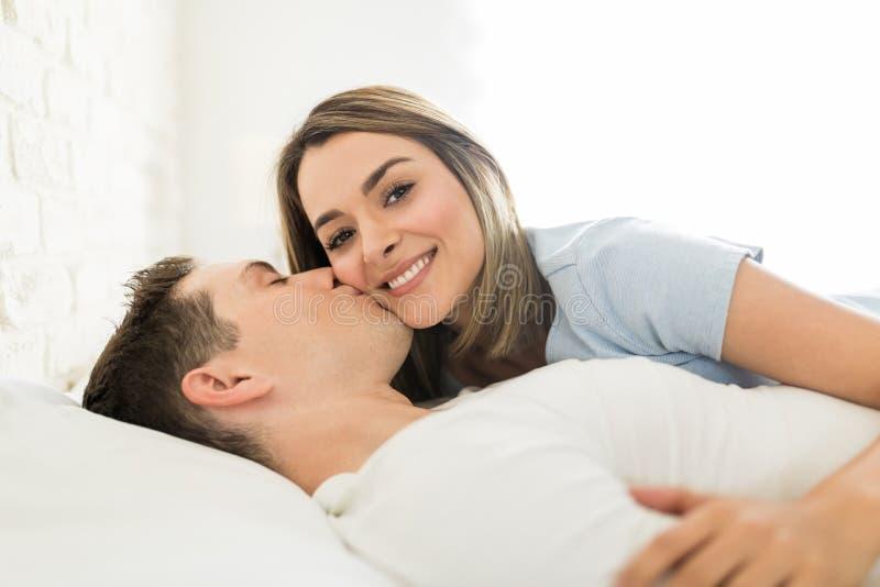 Attraktiv kvinna som kyssas av mannen på kind i säng royaltyfria bilder