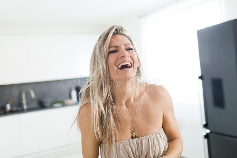 Attraktiv kvinna som ler i hennes k?k royaltyfri fotografi