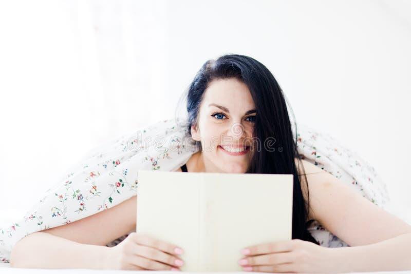 Attraktiv kvinna som ler, kopplar av och läsebok i sovrum fotografering för bildbyråer