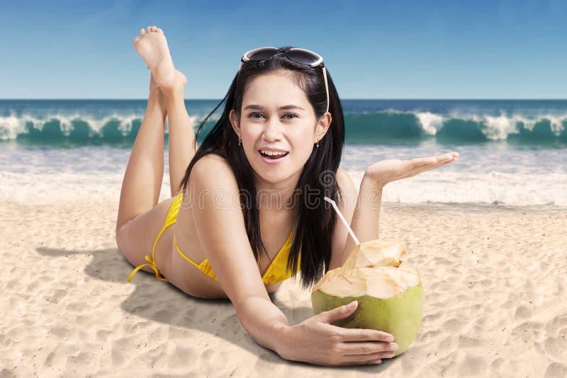 Attraktiv kvinna som ligger med kokosnötdrinken royaltyfri foto