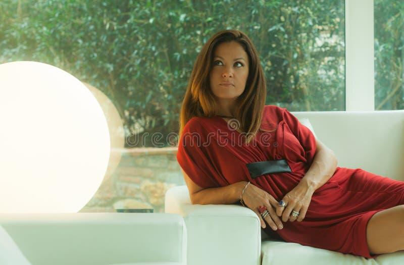 Attraktiv kvinna som ligger på en vit soffa royaltyfria bilder