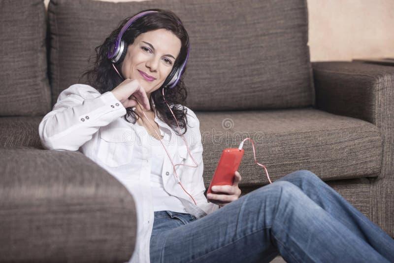 Attraktiv kvinna som lyssnar till musik royaltyfri foto