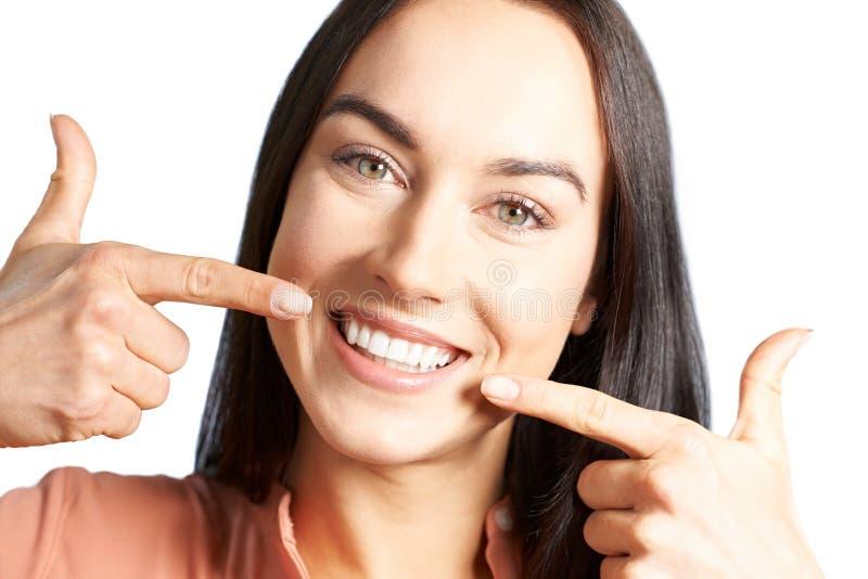 Attraktiv kvinna som pekar till hennes leende med perfekta vita tänder arkivbild