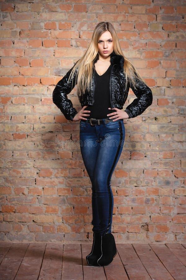 Attraktiv kvinna som poserar på nära väggen arkivfoto