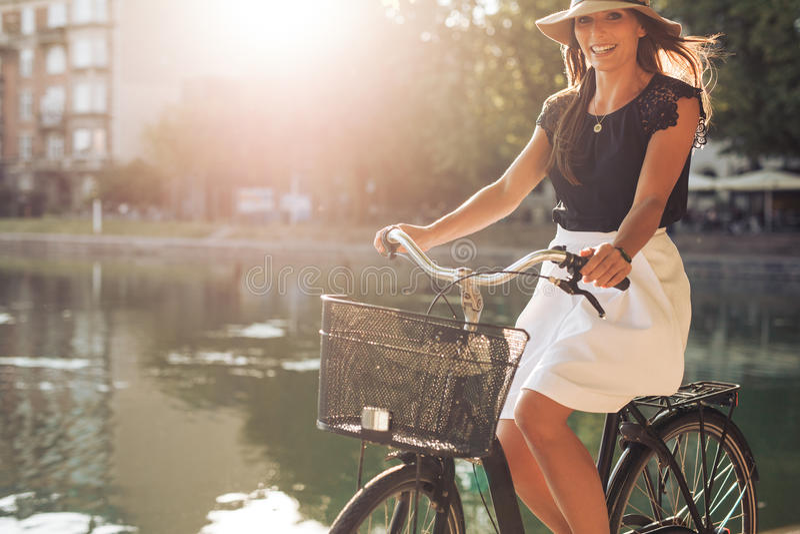 Attraktiv kvinna som rider en cykel vid ett damm arkivfoto