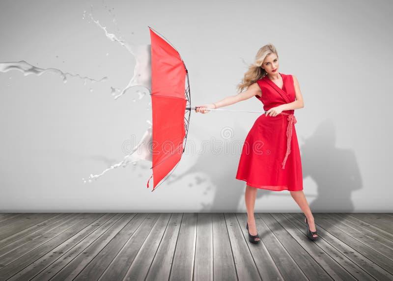 Attraktiv kvinna som rymmer ett paraply för att skydda sig från royaltyfri fotografi