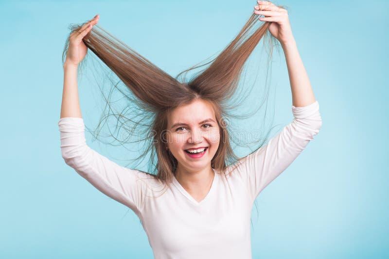 Attraktiv kvinna som rymmer till håret så lycklig och rolig flicka Isolerad blå bakgrund royaltyfri foto