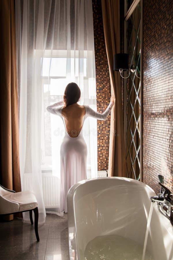 Attraktiv kvinna som ser fönstret och förbereder sig att ta ett bad royaltyfri bild