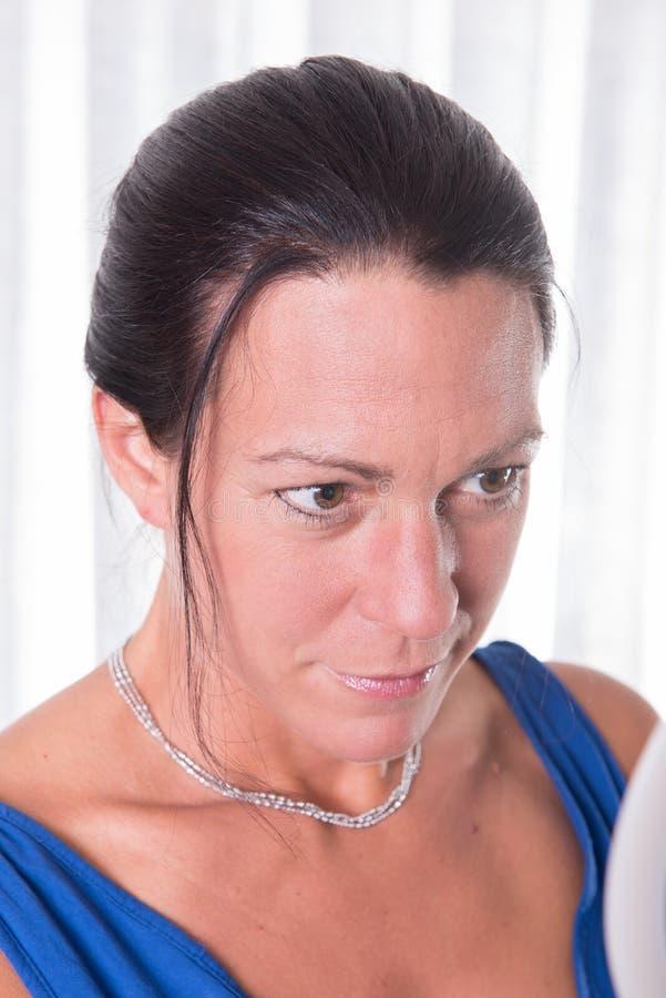 Attraktiv kvinna som ser in i spegeln arkivfoto