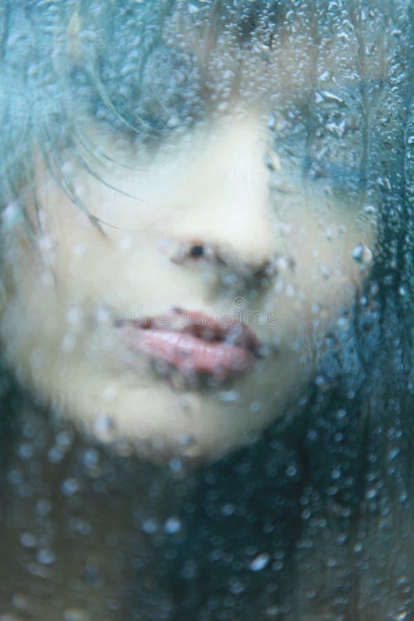 Attraktiv kvinna som ser ut ur fönstret på regnig dag arkivbilder