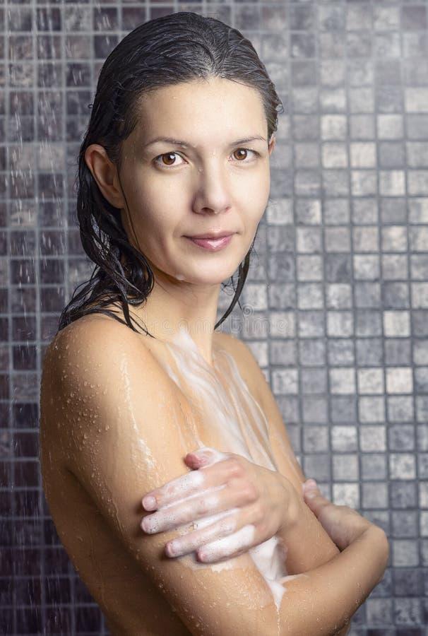Attraktiv kvinna som soaping sig i duschen royaltyfri fotografi