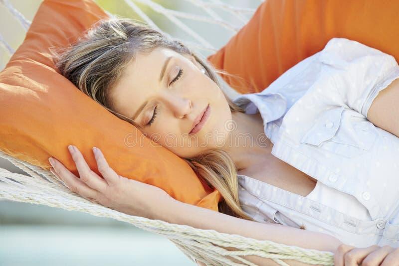 Attraktiv kvinna som sover i trädgårds- hängmatta royaltyfria bilder
