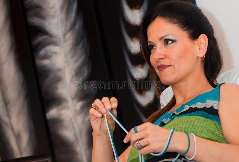 Attraktiv kvinna som spelar med en halsband i henne händer royaltyfri foto