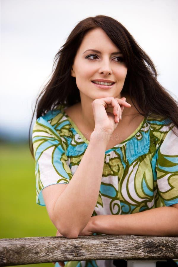 Attraktiv kvinna som står borttappad i tanke royaltyfri bild
