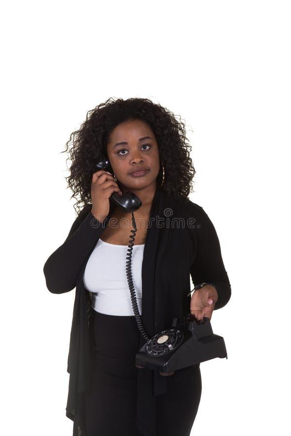 Attraktiv kvinna som talar på en roterande telefon för gammal tappning som isoleras på vit royaltyfri foto