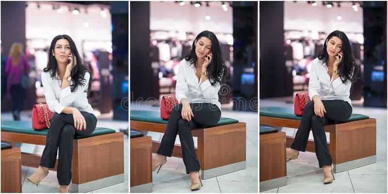 Attraktiv kvinna som talar på mobil i galleria Härlig trendig ung flicka i vitt manligt skjortasammanträde på träbänk arkivbild
